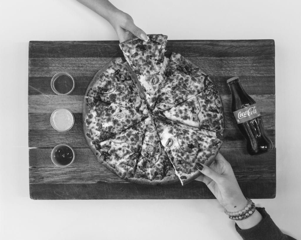 overhead shot of hands grabbing a piece of pizza with a bottle of coke next to them