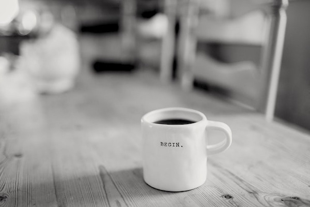 Coffee cup on a table with begin written on it